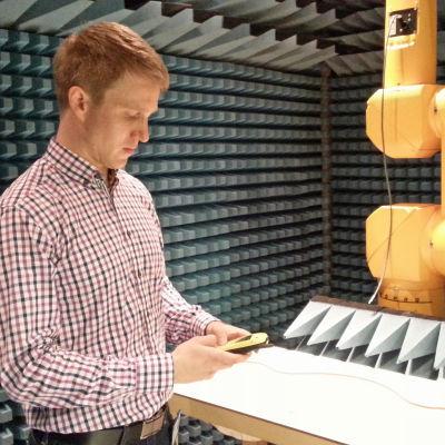 Forskare Sami Kännälä på Strålsäkerhetscentralen med mobiltelefon.