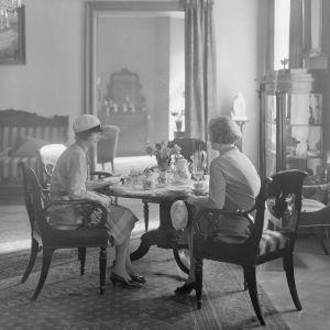 Svartvit bild på två kvinnor som sitter vid ett litet runt kaffebord på ett café.