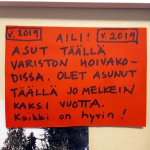 """punainen lappu jossa lukee: """" Aili, asut täällä Variston hoivakodissa..."""""""
