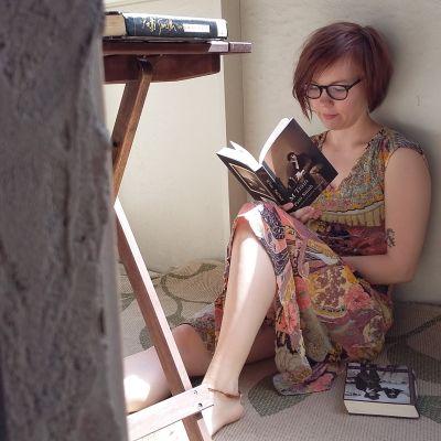 Ylva Perera läser M Train av Patti Smith på en balkong.