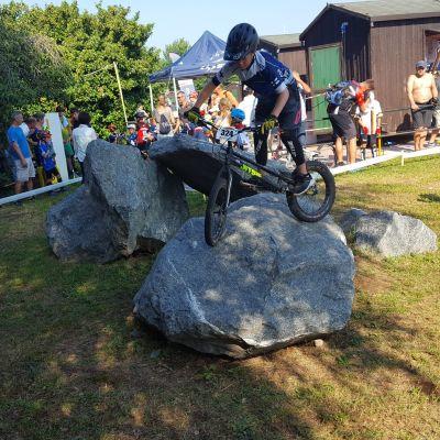 Pojke cyklar på en sten vid en gräsplan. Många följer med i publiken.