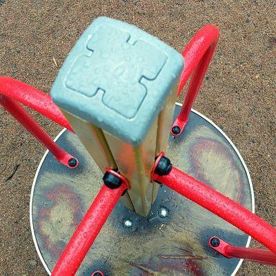 Lasten pieni karuselli leikkipuistossa kuvattununa ylhäältä päin. Karusellissa on neljä punaista kahvaa.