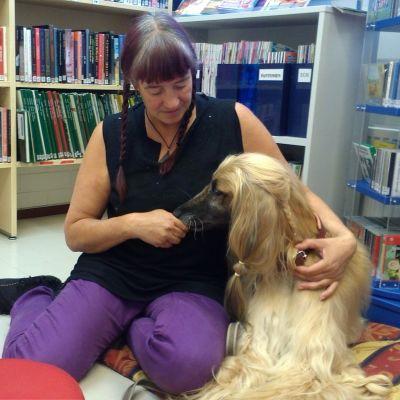 Läshunden Molly tillsammans med matte, biblioteksfunktionär Helena Österblad.