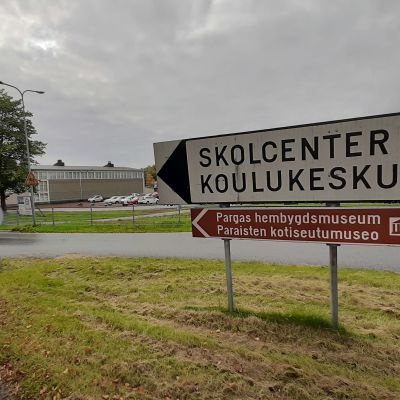 En vit vägskylt med texten Skolcenter Koulukeskus, och en brun skylt med texten Pargas hembygdsmuseum, i en vägkorsning med en skolbyggnad i bakgrunden.