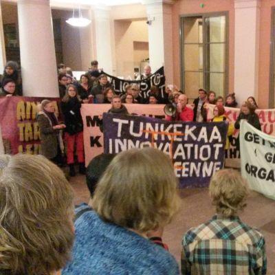 Helsingin yliopiston aulassa kajahtivat mielenosoittajien iskulauseet.