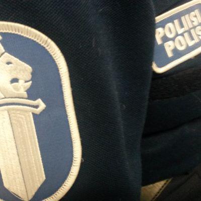 Poliisin hihamerkki ja poliisimerkki sinisessä virka-asussa.