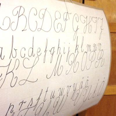 Kaunokirjoituksen aakkostaulu Regina-koulun ainoassa luokkahuoneessa