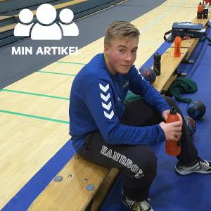 Handbollsmålvakten Lucas Lundström sitter på en bänk.