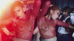 Läpinäkyvään toppiin pukeutunut nainen tanssii Studio 54 -klubilla. Kuva dokumentista Studio 54