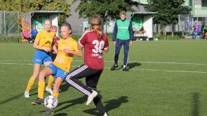 Två flickor fajtas om bollen i en fotbollsmatch.