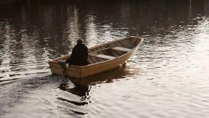 Man sitter i en båt med aktersnurra och åker bortåt från fotografen