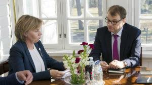 Anna-Maja Henriksson och Juha Sipilä sitter vid ett bord.