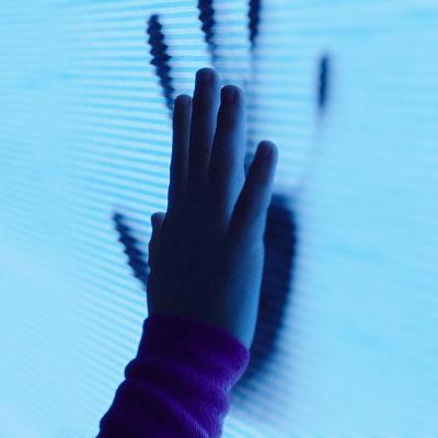 Barnskådeseplaren Kennedi Clements står med handflatorna tryckta mot en tv-skärm.
