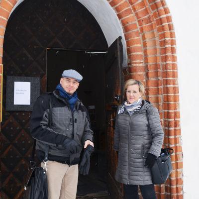 En man och en kvinna står utanför Borgå domkyrka. Kvinnan håller upp ytterdörren.