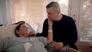 Kvinna ligger i en sjuksäng och en man sitter bredvid. De tittar på varandra och håller ena handen på varandras kinder.