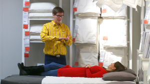 Nainen makaa patjalla kaupassa.