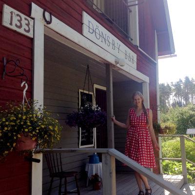 Nora Garusi står framför ett hus där det står på en skylt Dönsby B&B.