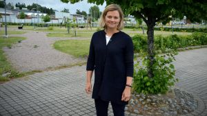 Erika Strandberg framför ett träd, en lekpark syns i bakgrunden.