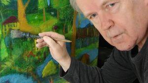 Vanhempi mies maalaa öljyväreillä maisemaa ja taloja.