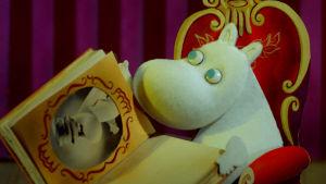 Mumintrollet sitter i en stol och tittar i ett gammalt fotoalbum på hans gamla släktingar.