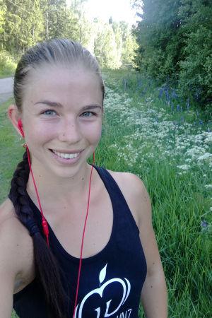 En kvinna iklädd träningskläder, med hörlurar i öronen. Hon står på en grusväg. Det ser ut som om hon är ute på en springtur.