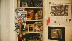 """Skafferi fullt med matvaror, utanför hänger två vimplar med texten """"Sumiainen"""" på."""
