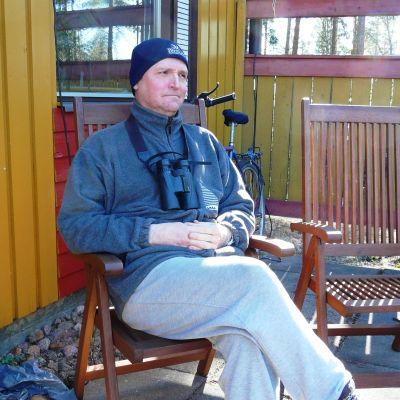 Magnus Östman, chefredaktör för Finlands natur, sitter på sin terrass och kikar på fåglar