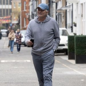 José Mourinho i casual-kläder (grå byxor, grå munkjacka) skrattande på en gata i London.