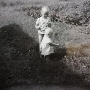 Kaksi pientä lasta kesäisellä nurmikolla vanhassa valokuvassa.