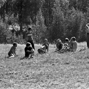 Ihmisiä istumassa nurmikolla Kunnasniemen entisen kansakoulun pihassa Kontiolahdella.