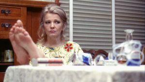 Mabel (Gena Rowlands) istuu jalat pöydällä ja tupakoi elokuvassa Naisen parhaat vuodet