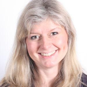 En kvinna med blont hår. Står framför en vit vägg och ler.
