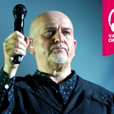 Peter Gabriel håller upp en mikrofon.