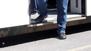 I bilden syns fötter & ben på en man som stiger av tåget.