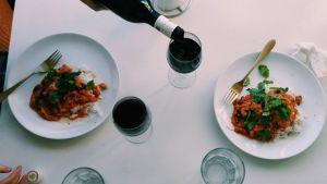 Två matportioner med rödvinsglas intill.