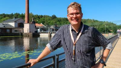 Porträtt av Ville Vuorelma som poserar mot broräcket på en bro i Svartån.