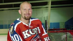 Jere Karalahti sitter på sargen iklädd en HIFK-tröja.