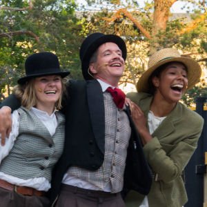 tre leende skådespelare på scen.
