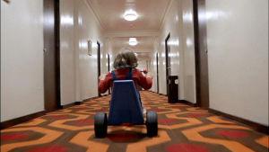 En liten pojke kör med en trampcykel i en tom hotellkorridor.