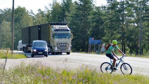 En cyklist cyklar på en riksväg. Bakom cyklisten skymtar en stor långtradare.