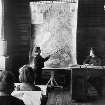Koululainen osoittaa karttakepillä Suomen karttaa.