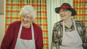 Kaksi nauravaa vanhempaa rouvaa esiliinoihin pukeutuneina.