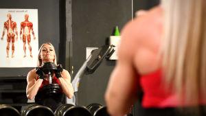 Linda Sonntag lyfter hantlar framför spegel i gymmet