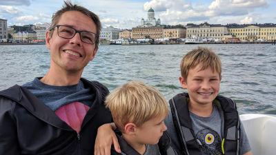 Olof och hans två barn sitter i en båt med Helsingfors i bakgrunden.
