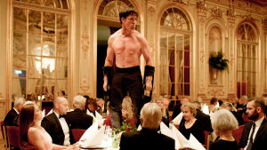 Oleg (Terry Notary) seisoo illallispöydän päällä ilman paitaa elokuvassa The Square
