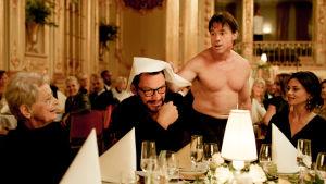 Apinamies häiritsee illallisseuruetta. Kohtaus elokuvasta The Square.