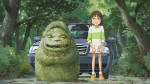 Kuva Henkien kätkemä -elokuvasta. Tyttö seisoo sammaloituneen jumalpatsaan vieressä, takana on moderni auto.