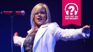 Samantha Fox står bakom en mikrofonställning och hon har armarna utsträckta åt sidorna.