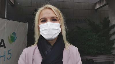 Porträttfotografi av kvinna i 40-årsåldern, blont hår och vitt munskydd. Hon har svart halsduk och ljusrosa kappa. Hon står utomhus framför en husvägg.