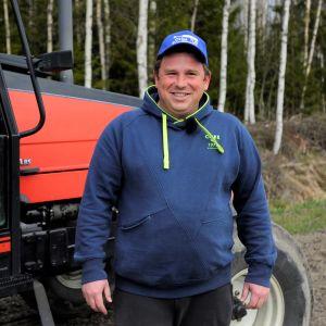 Vasyl Liutenko är säsongsarbetare från Ukraina. Står framför en traktor på en jordgubbsodling i Pörtom, Närpes, där han jobbar.